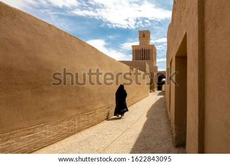 Ancient street with wind tower in the background, in Abarkuh, Iran