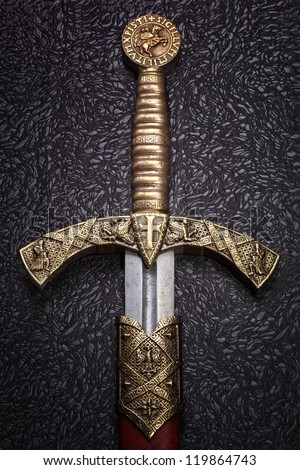 Ancient sword with the bronze handhold on a  beautiful dark background