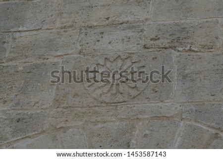 ancient symbol of the sun on the old stone wall