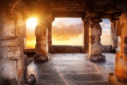 Ancient temple with columns at sunset sky background in India