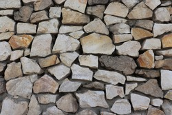 Ancient textured stonewall background. Rough weathered stonework surface wallpaper