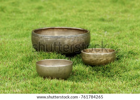 Ancient Tibetan singing bowls on green grass. Singing bowls for sound therapy. #761784265