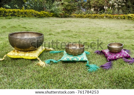 Ancient Tibetan singing bowls on green grass. Singing bowls for sound therapy. Singing bowls on colored pads. #761784253