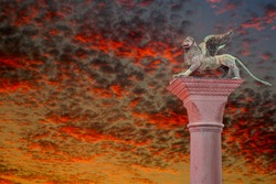 Ancient top tower sculpture of symbol of Venice winged lion at the Piazza San Marco at bloody red sunset with copy space for text, Venice, Italy, closeup, details