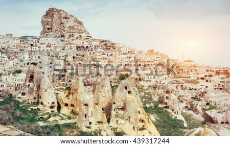 Ancient town and a castle of Uchisar dug from a mountains after sunrise, Cappadocia, Turkey #439317244
