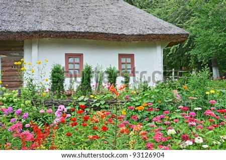 Ancient traditional ukrainian rural hut and flowerbed