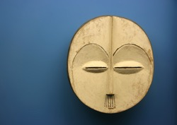 Ancient tribal mask over blue background