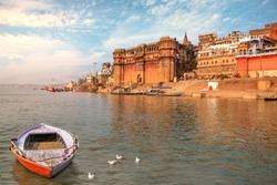 Ancient Varanasi India city architecture with view of Ganges river ghat at sunset. Wooden boat seen on river Ganga with migratory birds