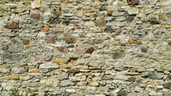 Ancient wall with stones, cobblestones and bricks. Close-up texture.