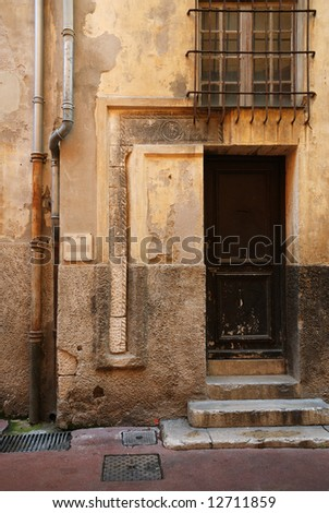 Ancient walls with close door and bars on window, some stone footsteps, Nice, France