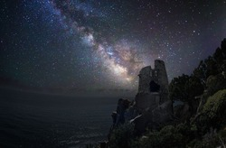 Ancient watchtower perched on the coast under the milky way