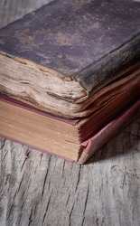 Ancient weathered books on wooden table, close-up
