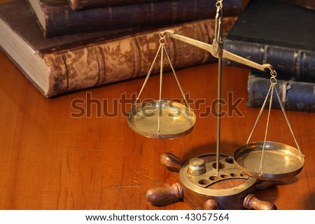Ancient weight scale standing on wooden table near old books - stock photo