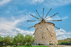 Ancient windmill in Golyazi (uluabat) bursa and it main structure made of stone and with wooden propeller with magnificent blue sky and green trees background during spring time