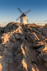 Ancient windmill in the town of Consuegra (Spain), on the route of the Don Quixote and Cervantes mills, at sunset.