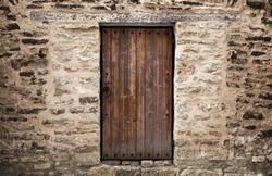 Ancient wooden door in stone castle wall. Tallinn, Estonia