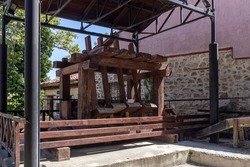 Ancient, wooden machine for the production of gunpowder in the park of the city of Eddesa (Central Macedonia, Greece) on a sunny, summer day