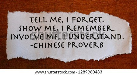 ancient words of wisdom on paper with torn edges and wood background #1289980483