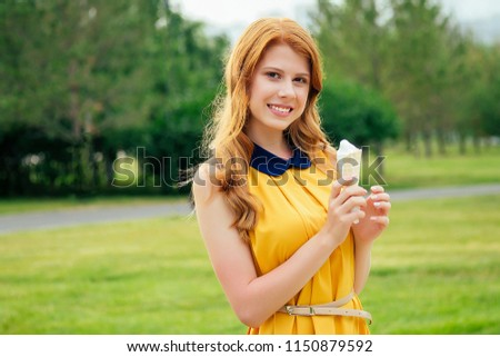 and beautiful young ginger redhead norwegian woman in a yellow dress eating vanilla ice cream in a waffle cone in the park