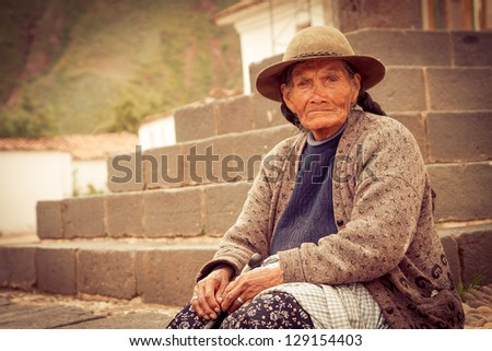 ANDAHUAYLILLAS PERU -JANUARY 15: Quechua woman begs for money at the main church in Andahuaylillas, Peru on January 15, 2013. Andahuaylillas is a popular destination for tourism from Peru. - stock photo