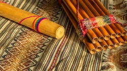 Andean instruments, Peruvian zampoña and rain stick on peruvian poncho. Natural light. Concept of traditional instruments.