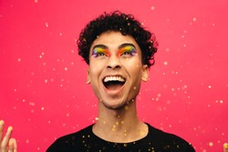 Androgynous male with rainbow eye makeup throwing up the glitter and laughing. Excited gay man with glitters flying against red background.