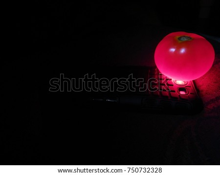 android mobile phone with tomato on it in glowing red color. this can be used as a technology background theme. it can be used for addiction, cyber security, hacking, network. night dark light time. #750732328