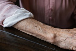 Anf elderly woman grandmother's arm with wrinkles and age spots.