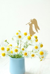 angel and white chamomile flowers. religious church holiday. concept of faith, Christianity. religion symbol