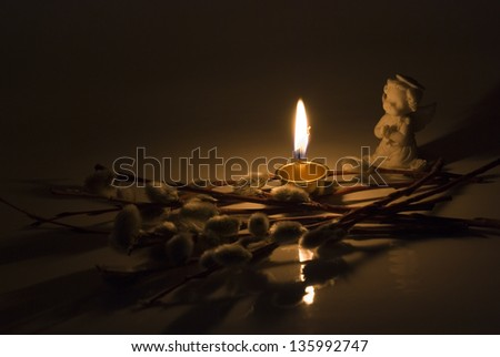 Angel, burning candle and willow twigs