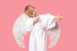 Angel Cherub child boy with large white wings is aiming at man to make him fall in love. Studio shot postcard on pastel pink background. Concept for Valentine Day 14 February.