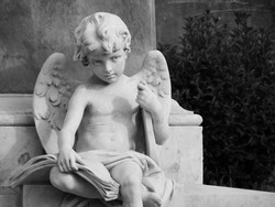 Angel child statue holding a lyre under his arm and a book on his knees. From Baroque town of Noto, Sicily.
