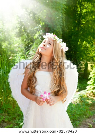 Angel children girl in forest with flower in hand looking sky [Photo Illustration]