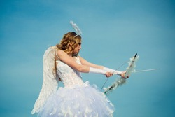 Angel children girl with white wings. Innocent Girl with angel wings standing with bow and arrow against blue sky and white clouds. Teen angel.