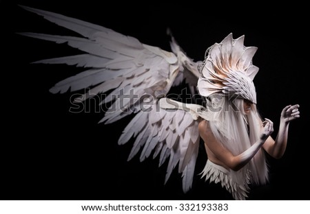 Stock Photo Angel, costume, concept, cinematic, young girl with white wig , which carries a large white mask and a large white wings. feathers costume and hands painted in white, dramatic , thoughtfull