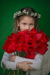 Angel girl in white clothes, white feather wings and wreath of natural cherry flowers on her head hugging large bouquet of red tulips. Corners of the photo are overlaid with barely noticeable texture.