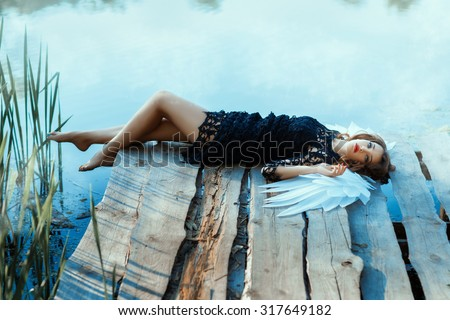 Angel girl lying on the pier. It looks beautiful and sad. See more photos of this series.