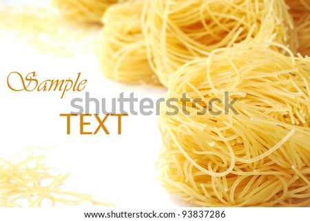 Angel hair pasta nests on white background with copy space.  Macro with shallow dof.