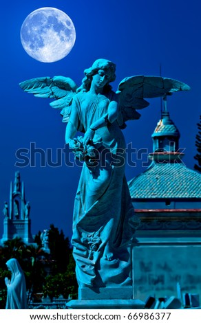 Angel in a cemetery at midnight with a bright full moon