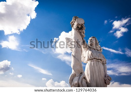 Angel in light: old angel sculpture against bright blue sky and white clouds. Copy space.