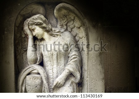 Angel on vintage tombstone on old cemetery