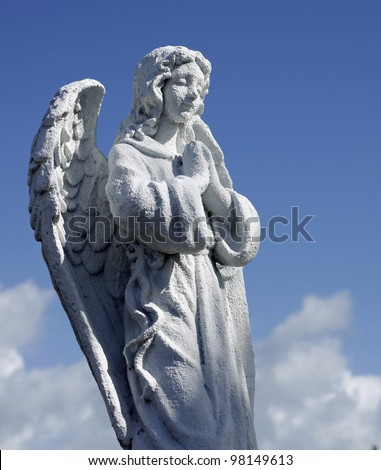 Angel statue against blue sky.
