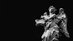 Angel statue holding Jesus Inri sign. A 17th century baroque masterpiece at the top of Sant'Angelo Bridge in the center of Rome (Black and White with copy space)
