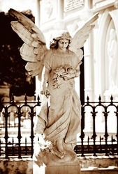 Angel statue on a cemetery in golden tones