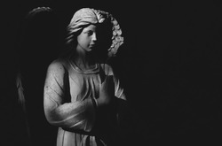 Angel statue praying in light and shadow. Black and white image.