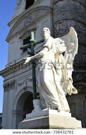 Angel statue with a cross and snake in front of