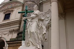 Angel statue with cross in front of Karlskirche (St. Charles's Church). An angel with wings holds a cross with a snake in his hands. The sculpture is located near the old church in Vienna.