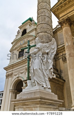 Angel statue with cross in front of Karlskirche (St. Charles's Church), Vienna, Austria