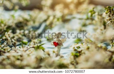 Angel. White statue of angel. Small statue with heart. Spring fruit trees white flowers photo. Natural wooden background with white flowers fruit trees and space for text #1072780007