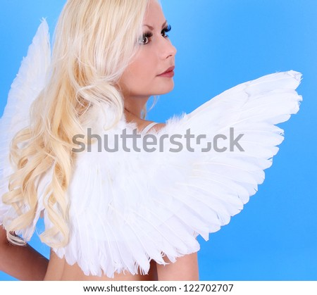 angel wings on girl, beautiful blonde over blue background, backside
